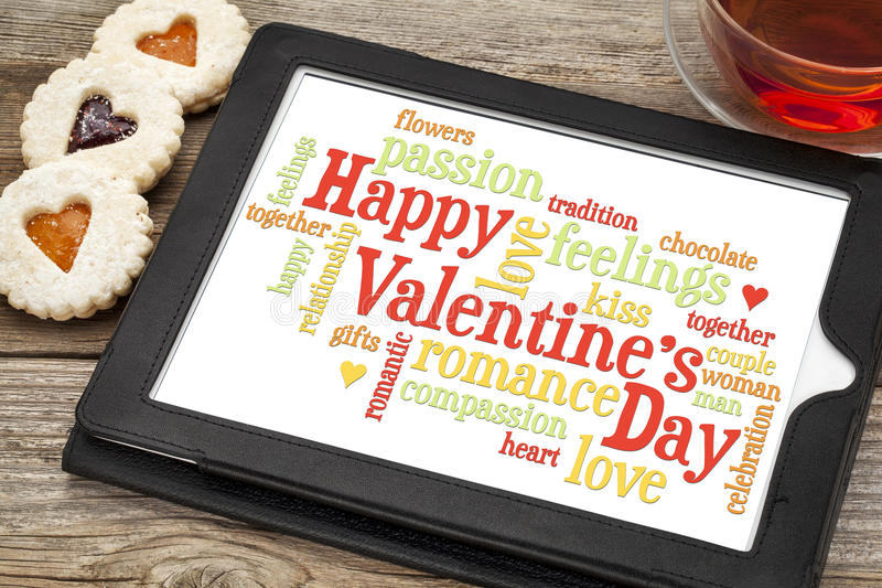 Happy Valentines Day. Word cloud on a digital tablet with heart cookies and a cup of tea stock images