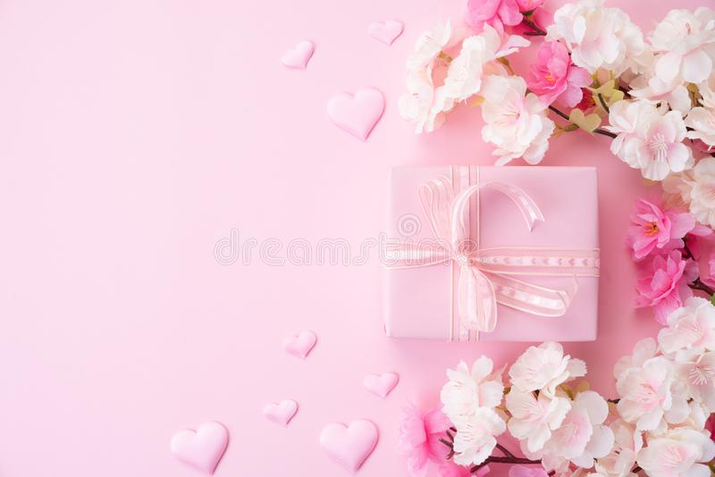 Happy valentines or mothers day concept. pink flower with paper heart and gift box on pink pastel background royalty free stock image