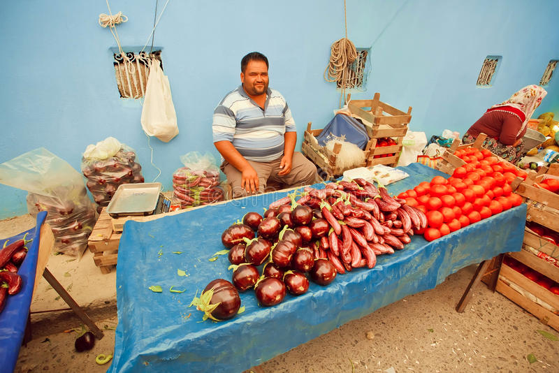Happy vegetable trader waiting for customers with eggplant and tomatoes on rural market in Turkey royalty free stock image