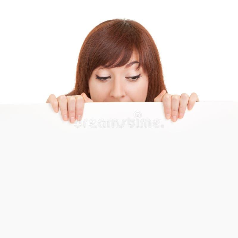 Happy verblüffte Frau mit weißem, weißes, weißes Brett auf weiß isoliertem Brett Modell in Studio-Holding-Papier-Plakat Vergnügun lizenzfreie stockfotografie