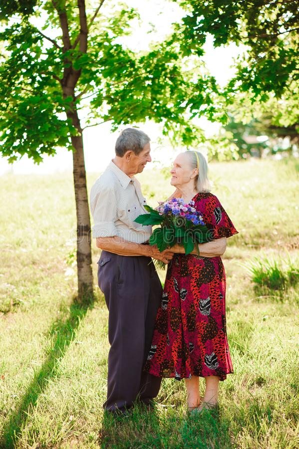 Happy and very old couple smiling in a park on a sunny day. royalty free stock image