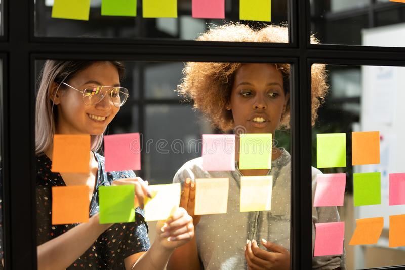Happy vietnamese employee working with concentrated african american trainee. stock photography