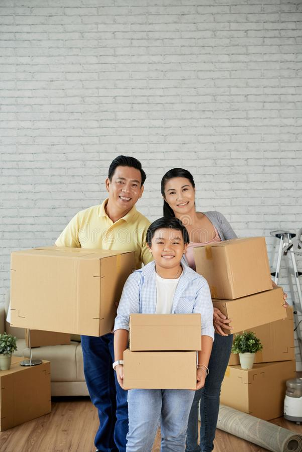 Family moving out. Happy Vietnamese family of three holding cardboard boxes and smiling at camera royalty free stock photos