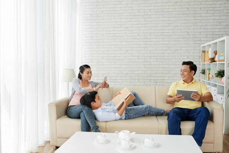 Family resting on sofa. Happy Vietnamese family of three resting on comfortable sofa at home stock photos
