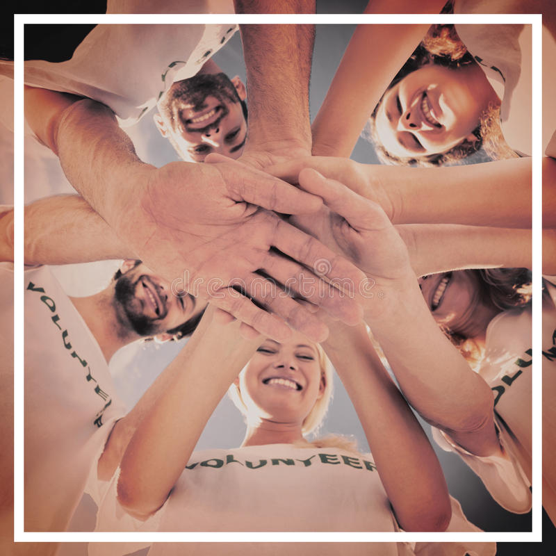 Happy volunteers with hands together against blue sky stock image