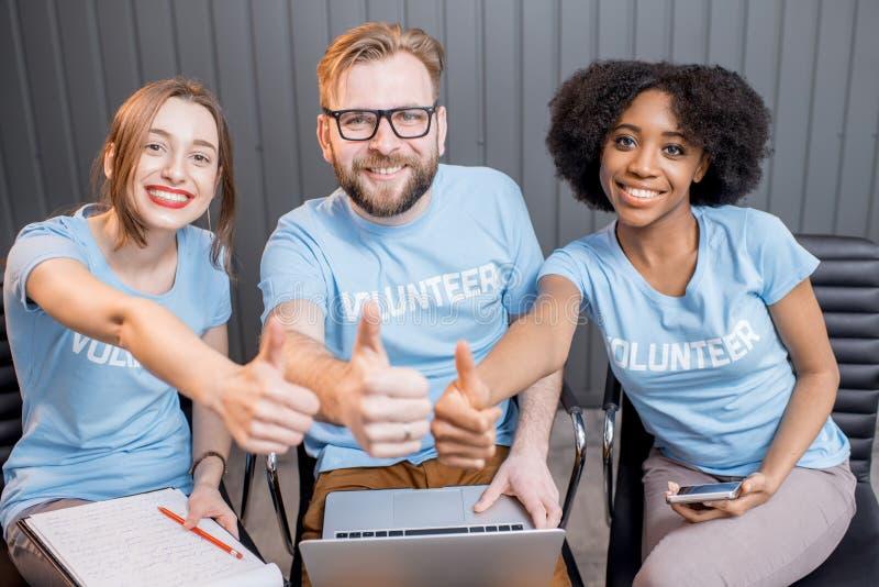 Happy volunteers indoors stock photos