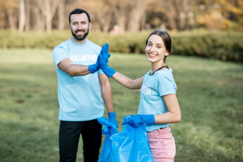 Happy volunteers in the paark stock image
