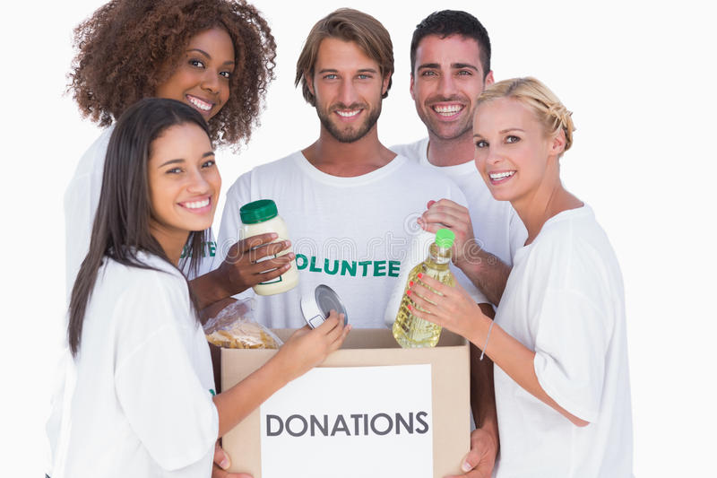 Happy volunteers putting food in donation box stock images