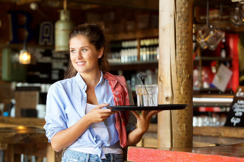 Happy waitress standing at the bar holding drinks royalty free stock photo