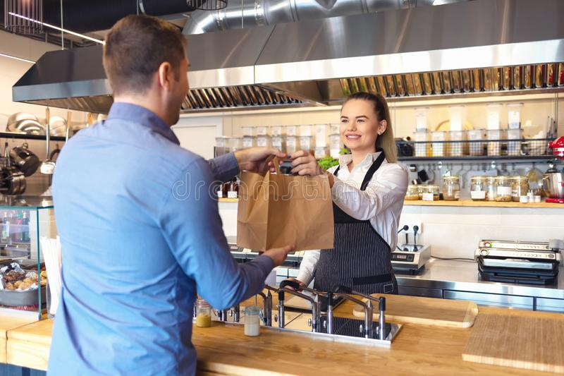 Happy waitress waring apron serving customer at counter in small family eatery restaurant stock images