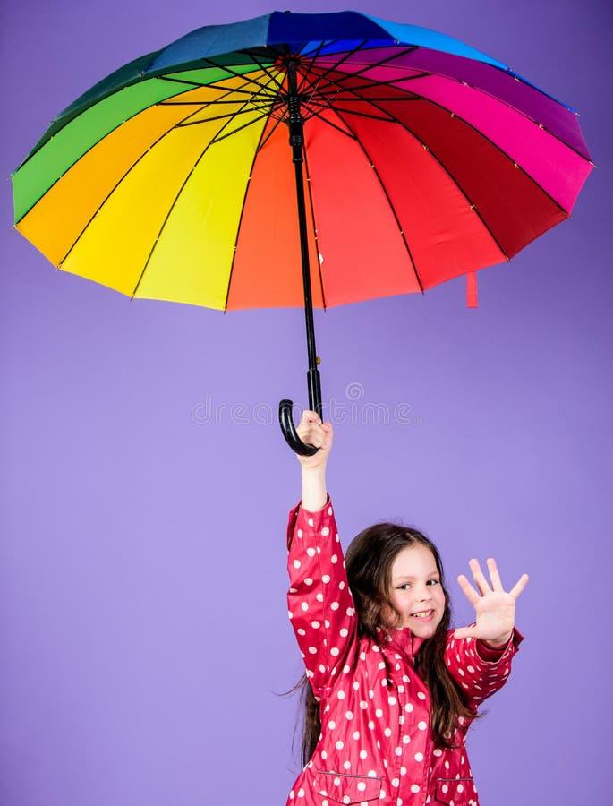 Happy walk under umbrella. Enjoy rain concept. Kid girl happy hold colorful rainbow umbrella. Rainy weather with proper stock images