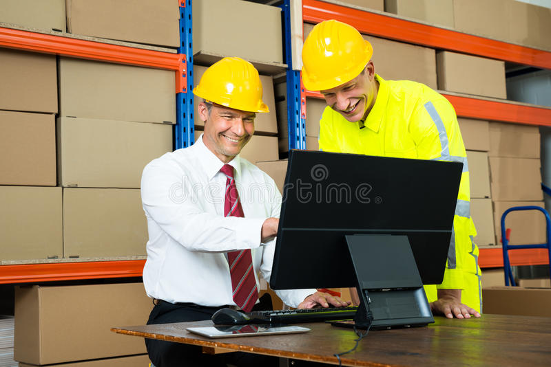 Happy Warehouse Worker And Manager Using Computer. Portrait Of Happy Warehouse Worker And Manager Using Computer In A Warehouse stock images