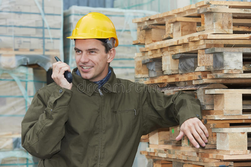 Happy warehouse worker with radio transmitter. One young smiling warehouse manager worker speaking on radio transmitter near wood pallet royalty free stock photos