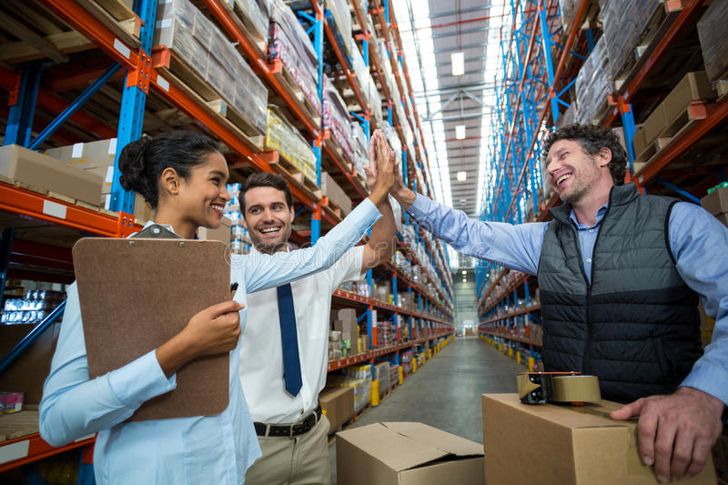Happy warehouse workers giving high five stock image