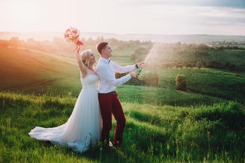 Happy wedding couple with buttle of champaine and splashes of champagne. Lifestyle,fun royalty free stock images