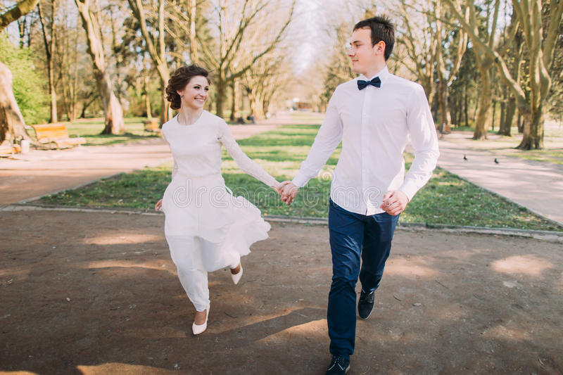 Happy wedding couple charming groom and blonde bride running with joined hands on city park road stock image
