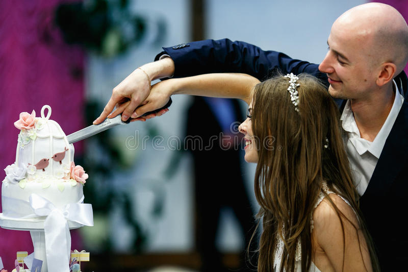 Happy wedding couple cut cake at the first time royalty free stock photography