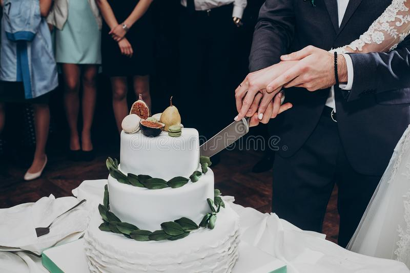 Happy wedding couple cutting together wedding cake. rustic cake with greenery pear and figs and macaroons at luxury wedding. Reception in restaurant. expensive stock image