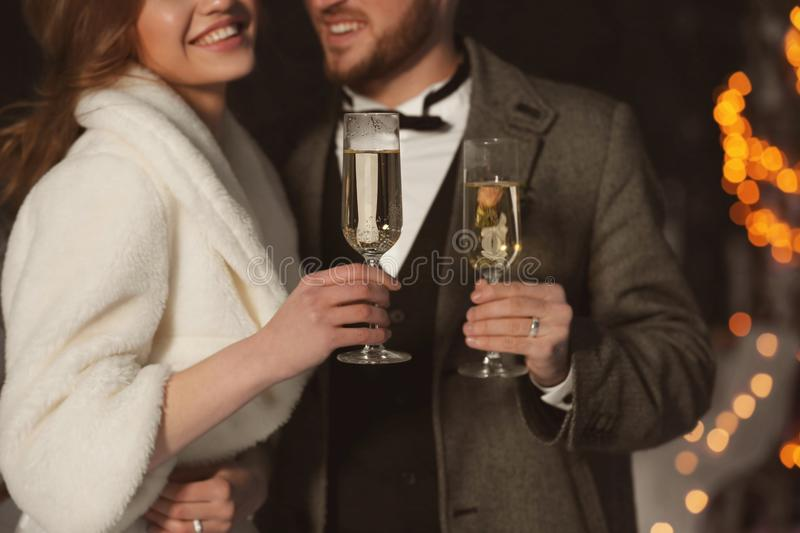 Happy wedding couple with glasses of champagne. On winter evening, closeup stock image