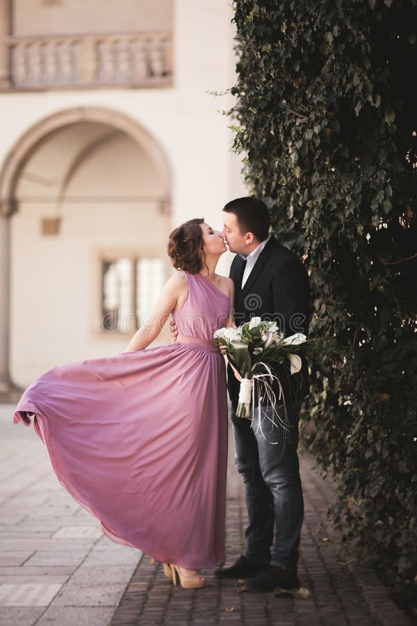 Happy wedding couple, groom, bride with pink dress hugging and smiling each other on the background walls in castle.  royalty free stock images