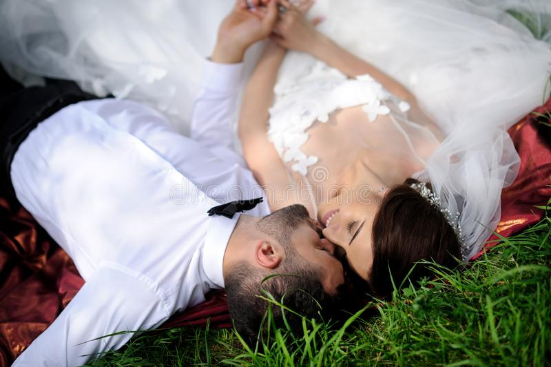 Happy wedding couple lying on green grass at the summer time stock photography