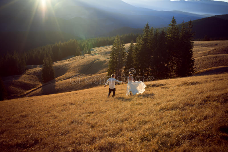 Happy wedding couple running and having fun on the field surrounded by mountains stock images