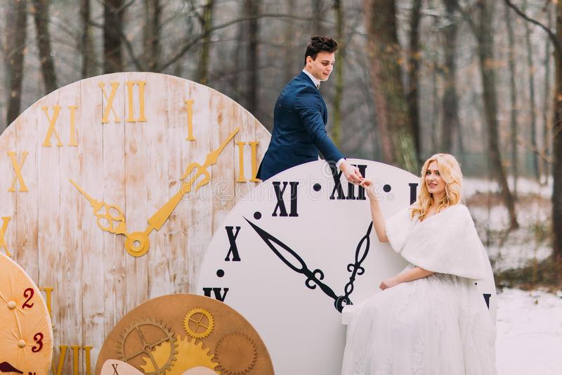 Happy wedding couple softly holding hands at the big vintage clocks in autumn forest. Creative decorations stock photography
