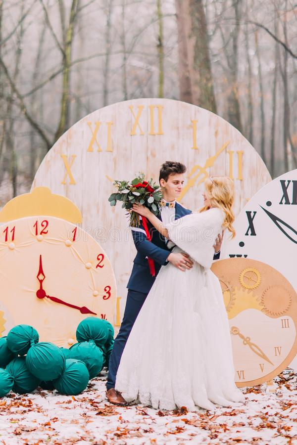 Happy wedding couple softly hugs at the big vintage clocks in autumn forest. Creative decorations stock photography
