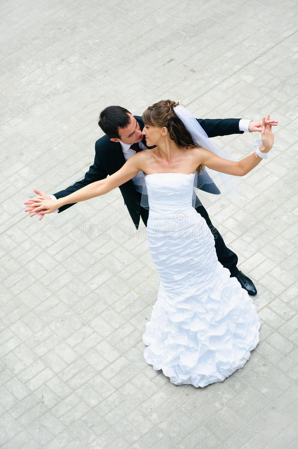 Happy wedding couple standing, kisses and holding hands stock photos