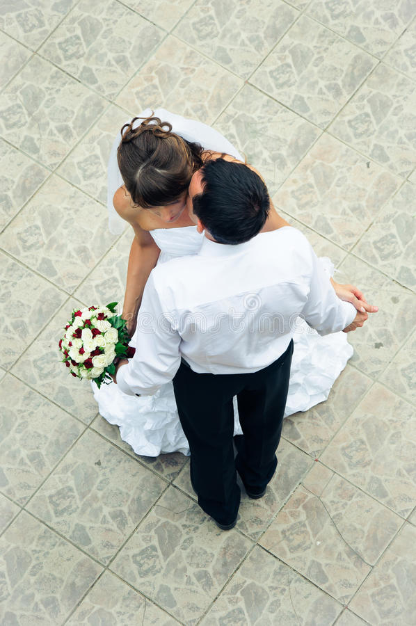 Happy wedding couple standing, kissing and holding hands stock images