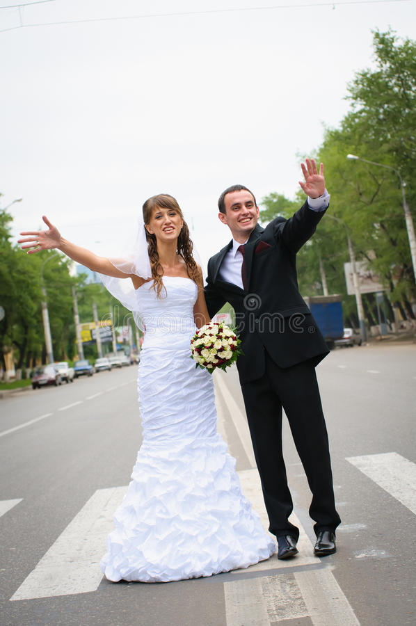 Happy wedding couple standing for a road and wave hands royalty free stock photos
