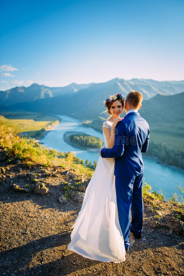 Happy wedding couple staying over the beautiful landscape with mountains stock image