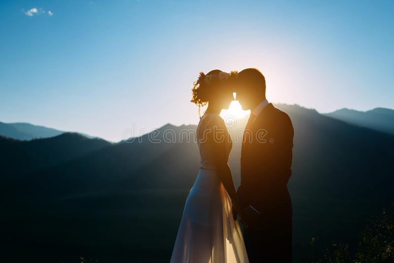 Happy wedding couple staying and kissing over the beautiful landscape with mountains stock photography