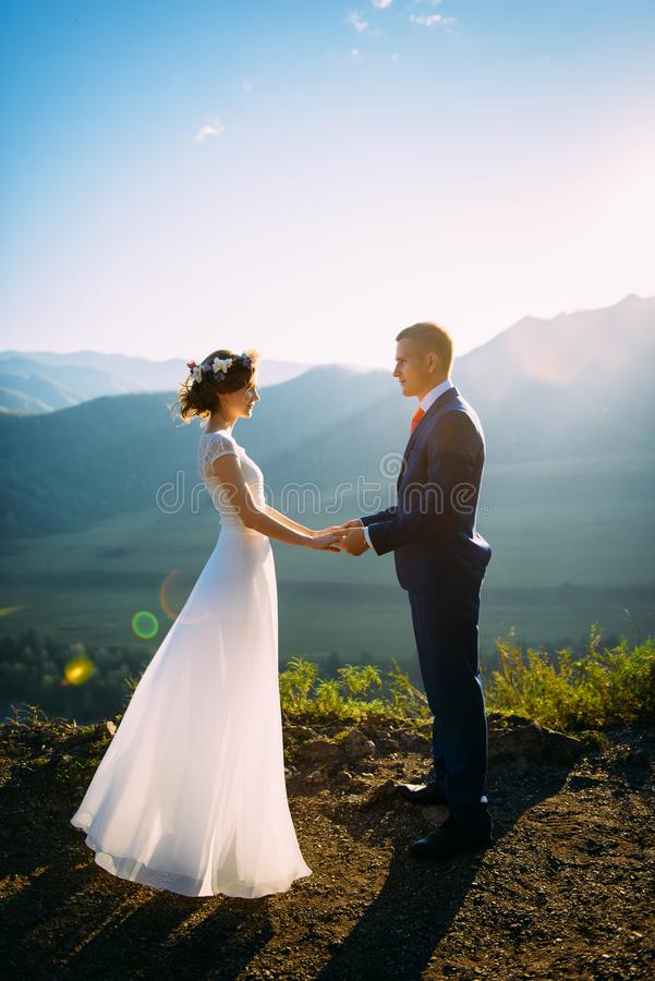 Happy wedding couple staying over the beautiful landscape with mountains royalty free stock images