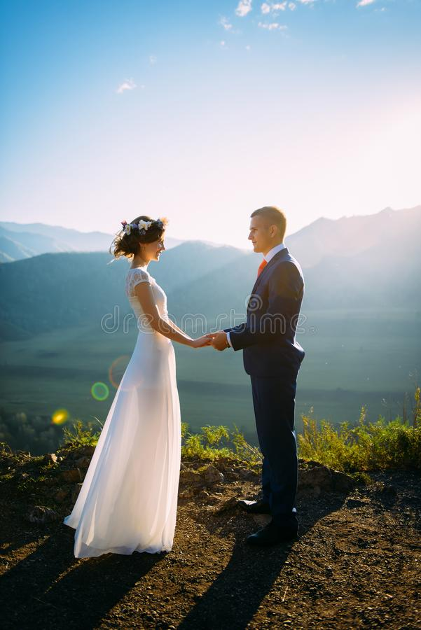 Happy wedding couple staying over the beautiful landscape with mountains royalty free stock photography