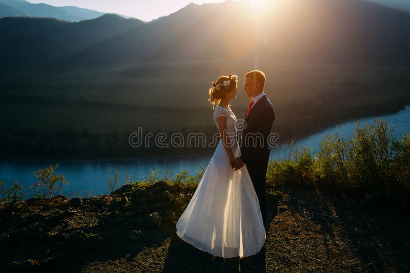 Happy wedding couple staying over the beautiful landscape with mountains royalty free stock photo