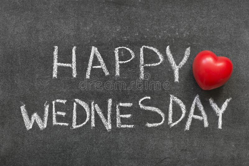 Happy Wednesday. Phrase handwritten on blackboard with heart symbol instead of O stock photography