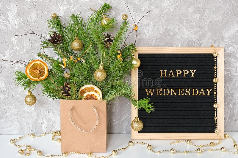 Happy Wednesday text on black letter board and festive bouquet of fir branches with christmas decor in craft package on table. Template for postcard, greeting royalty free stock photos