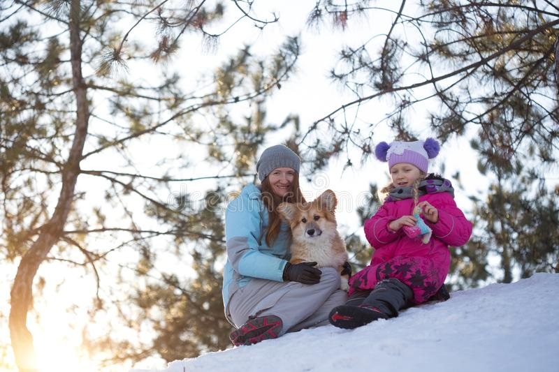 Girls and corgi fluffy puppy portrait. Happy weekend - mom and daughter with little cute corgi fluffy puppy at the outdoor. Winter stock image