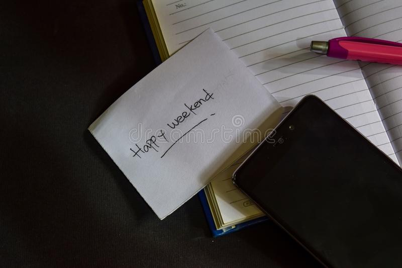 Happy Weekend word written on paper. Happy Weekend text on workbook, Black background concept royalty free stock photo