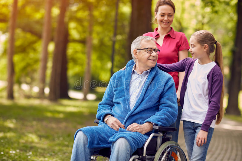 Happy wheelchair man with daughter and granddaughter stock photography