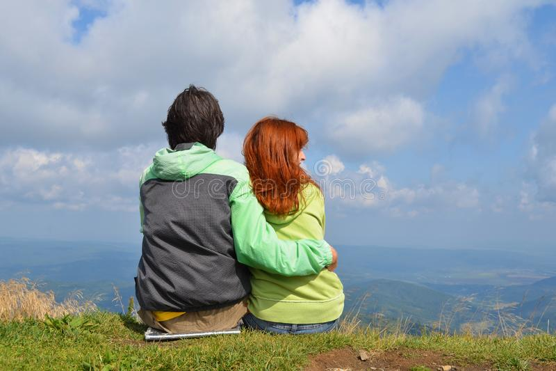 Happy white man and woman tourists in green clothes sitting hugging on edge of top of mountain and look into distance stock image