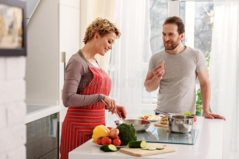 Happy wife cooking for husband. Cheerful married couple is standing in kitchen and smiling. Woman is frying food on pan. Man is eating vegetable and looking at stock photography
