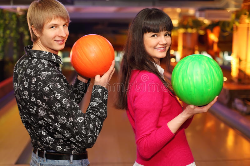 Happy wife and husband with balls in bowling club stock image