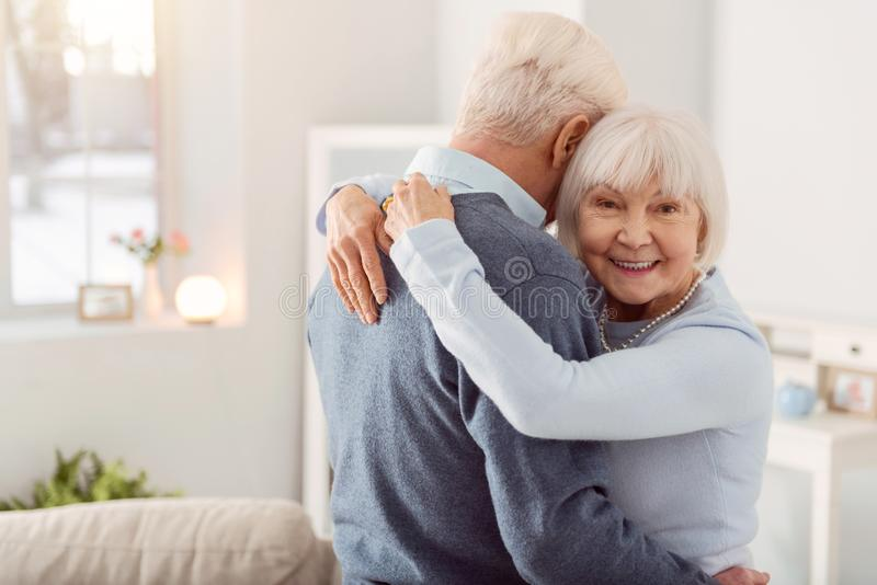 Cheerful elderly woman posing while hugging her husband. Happy wife. Pleasant elderly women smiling at the camera while hugging her beloved husband during the stock image