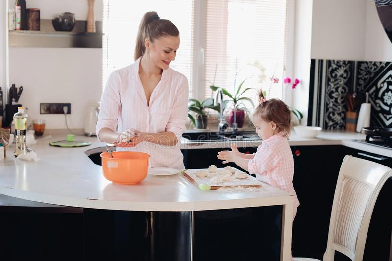 Little lovely kid helping parent with dough at kitchen. Happy wife smiling and preparing breakfast together with child for husband. Beautiful mother with cute stock images