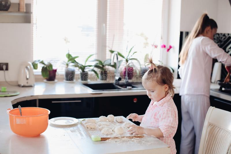 Little lovely kid helping parent with dough at kitchen. Happy wife smiling and preparing breakfast together with child for husband. Beautiful mother with cute stock photo
