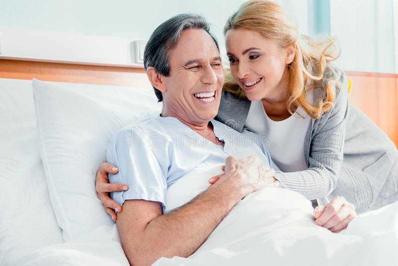 Happy wife visiting elderly husband in hospital stock photo