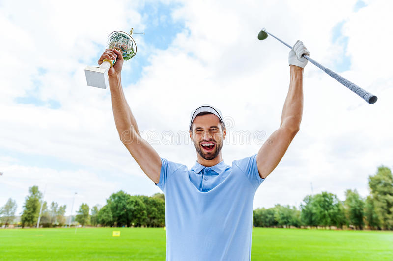 Happy winner. Happy male golfer holding trophy and driver while standing on golf course royalty free stock photography