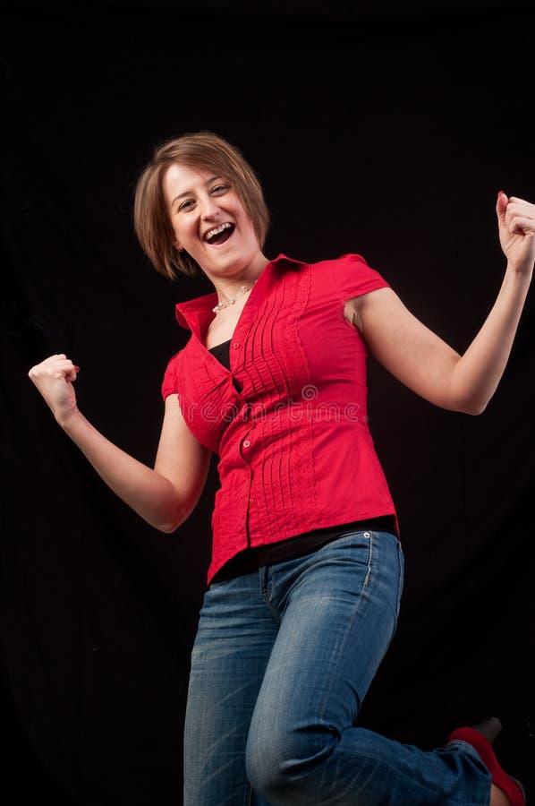 Happy winning success woman celebrating by dancing. Beautiful yo royalty free stock photo